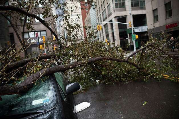 NEW YORK, NY - OCTOBER 30:  A car crushed by a tree following Hurricane Sandy on October 30, 2012 in the Financial District of New York, United States. The storm has claimed at least 16 lives in the United States, and has caused massive flooding across much of the Atlantic seaboard. US President Barack Obama has declared the situation a 'major disaster' for large areas of the US East Coast including New York City. Photo: Andrew Burton, Getty Images / Getty Images North America