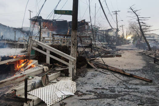 Damage caused by a fire at Breezy Point is shown Tuesday, Oct. 30, 2012, in in the New York City borough of Queen. The fire destroyed between 80 and 100 houses Monday night in the flooded neighborhood. More than 190 firefighters have contained the six-alarm blaze fire in the Breezy Point section, but they are still putting out some pockets of fire. Photo: Frank Franklin II, AP / AP2012