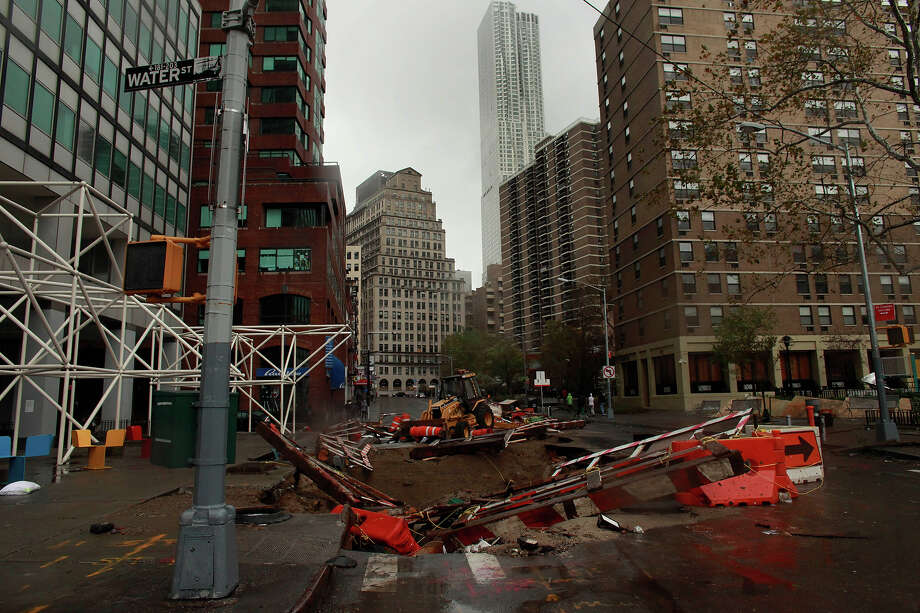 A construction site sinks into a large hole on South Street Seaport following Hurraicane Sandy October 30, 2012 in Manhattan, New York.The storm has claimed at least 16 lives in the United States, and has caused massive flooding across much of the Atlantic seaboard. US President Barack Obama has declared the situation a 'major disaster' for large areas of the US East Coast including New York City. Photo: Allison Joyce, Getty Images / 2012 Allison Joyce