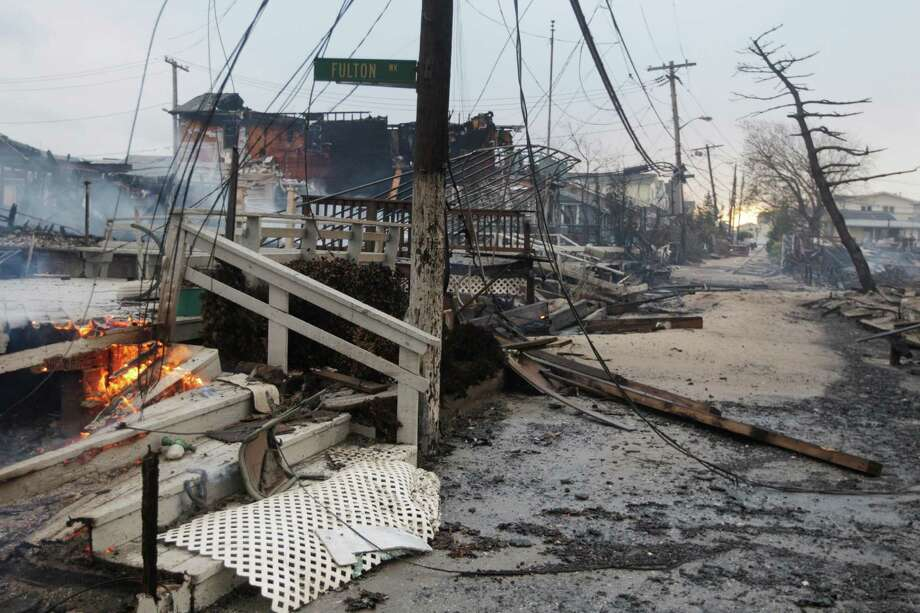 Damage caused by a fire at Breezy Point is shown Tuesday, Oct. 30, 2012, in in the New York City borough of Queen. The fire destroyed between 80 and 100 houses Monday night in the flooded neighborhood. More than 190 firefighters have contained the six-alarm blaze fire in the Breezy Point section, but they are still putting out some pockets of fire. Photo: Frank Franklin II, AP / AP