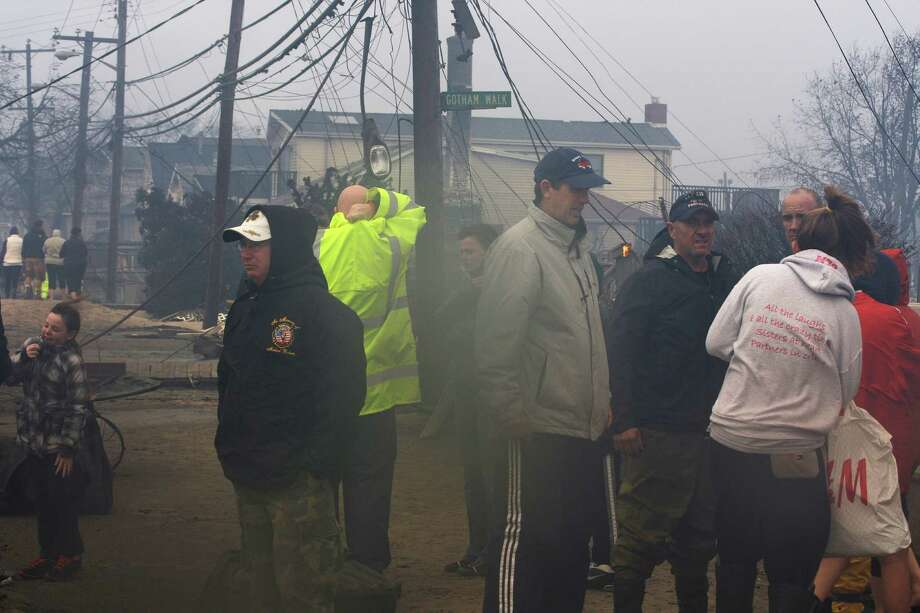 People assess damage caused by a fire at Breezy Point in the New York City borough of Queens Tuesday, Oct. 30, 2012. The fire destroyed between 80 and 100 houses Monday night in an area flooded by the superstorm that began sweeping through earlier. Photo: Frank Franklin II, AP / AP