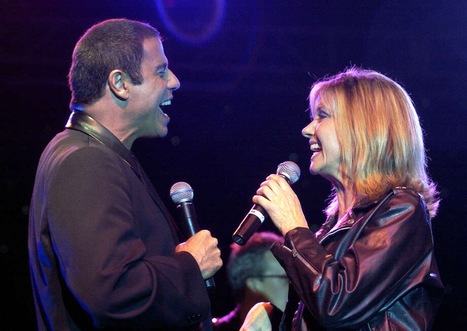 "John Travolta and Olivia Newton John sing at Paramount Home Entertainment's release of the movie; ""Grease'"" on DVD, in this 2002 file photo. Newton-John, who performs at the Majestic Theatre on Sunday, and Travolta have recorded a Christmas song. AP Photo: MICHAEL CAULFIELD, AP / WIREIMAGE.COM"