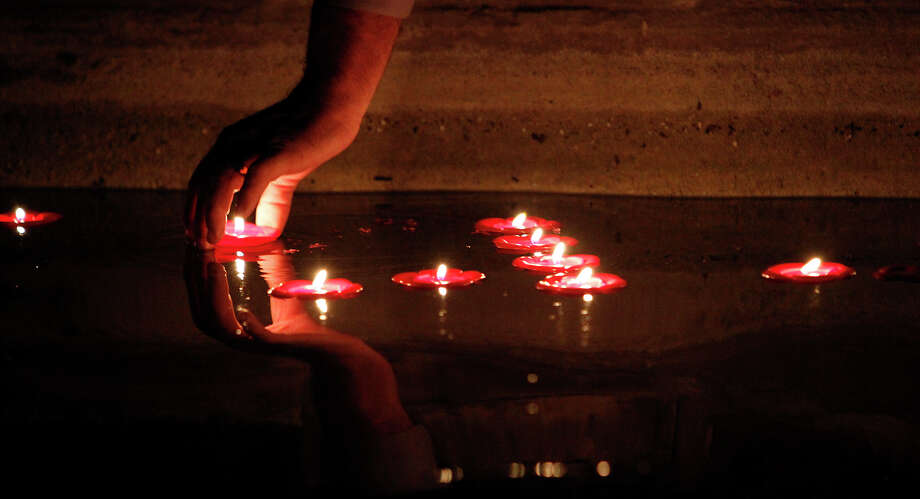 A participant places a lit diya, or candle, on the water's surface during a Diwali observance at HemisFair Park. Diyas signify the triumph of good over evil. Photo: Michael Miller, San Antonio Express-News / mmiller@express-news.net