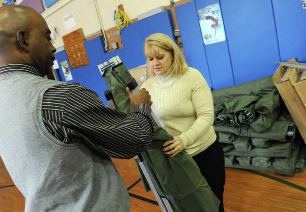 Garry Horne, director of community and emergency services, left, and Deputy Nan Welch fold up a cot to help break down the shelter in a gym at the Albany County Sheriff's Office, Public Safety & Community Resource Building on Tuesday, Oct. 30, 2012 in Clarksville, N.Y. Horne said the gym was full of people last night due to the impact of Hurricane Sandy. This building used to be the Clarksville Elementary School. (Lori Van Buren / Times Union) Photo: Lori Van Buren
