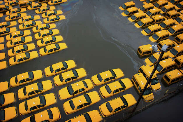 Across the river, a parking lot full of yellow cabs is flooded as a result of superstorm Sandy on Tuesday, Oct. 30, 2012 in Hoboken, NJ. Photo: Charles Sykes, AP / AP2012