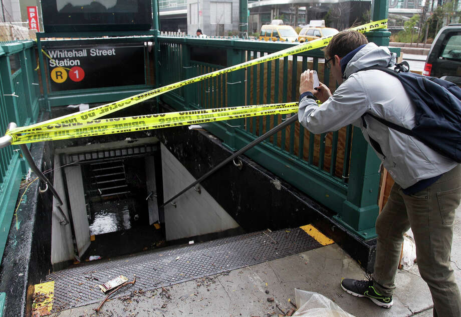 A man uses his mobile phone to photograph a closed and flooded subway station in lower Manhattan, in New York, Tuesday, Oct. 30, 2012. Due to superstorm Sandy, New York City awakened Tuesday to a flooded subway system, shuttered financial markets and hundreds of thousands of people without power a day after a wall of seawater and high winds slammed into the city, destroying buildings and flooding tunnels. Photo: AP