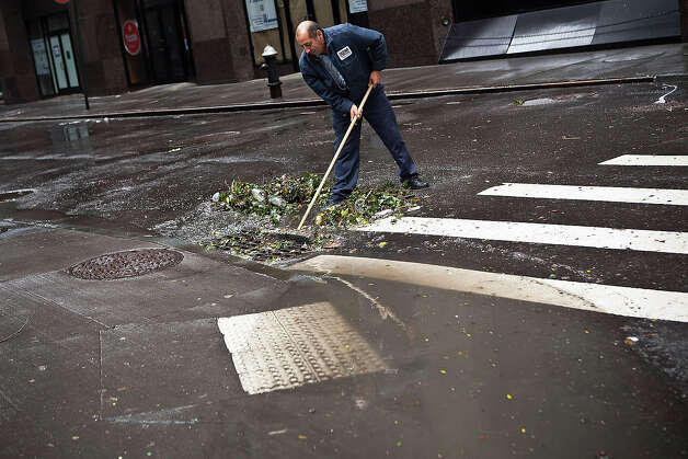 Ramiro Arcos sweeps debris from a storm drain while cleaning up damage caused by Hurricane Sandy on October 30, 2012 in the Financial District of New York, United States. The storm has claimed at least 16 lives in the United States, and has caused massive flooding across much of the Atlantic seaboard. US President Barack Obama has declared the situation a 'major disaster' for large areas of the US East Coast including New York City. Photo: Andrew Burton, Getty Images / 2012 Getty Images