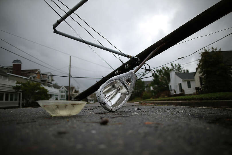 A street light and utility pole brought down from Hurricane Sandy lays on the street, on October 30,