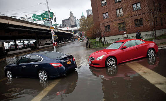 NEW YORK, NY - OCTOBER 30:  Cars are left parked on a flooded street, caused by Hurricane Sandy, on October 30, 2012, in the Lower East Side of New York City. The storm has claimed at least 16 lives in the United States, and has caused massive flooding accross much of the Atlantic seaboard. US President Barack Obama has declared the situation a 'major disaster' for large areas of the US East Coast including New York City. Photo: Andrew Burton, Getty Images / 2012 Getty Images