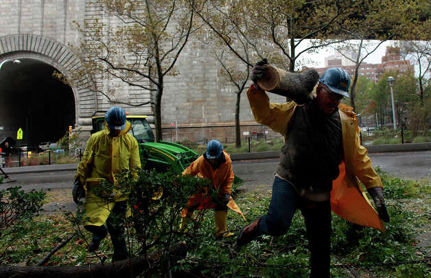 Workers clean up a fallen tree October 30, 2012 in New York City. The storm has claimed at least 16 lives in the United States, and has caused massive flooding across much of the Atlantic seaboard. US President Barack Obama has declared the situation a 'major disaster' for large areas of the US East Coast including New York City, with wide spread power outages and significant flooding in parts of the city. Photo: Allison Joyce, Getty Images / 2012 Getty Images