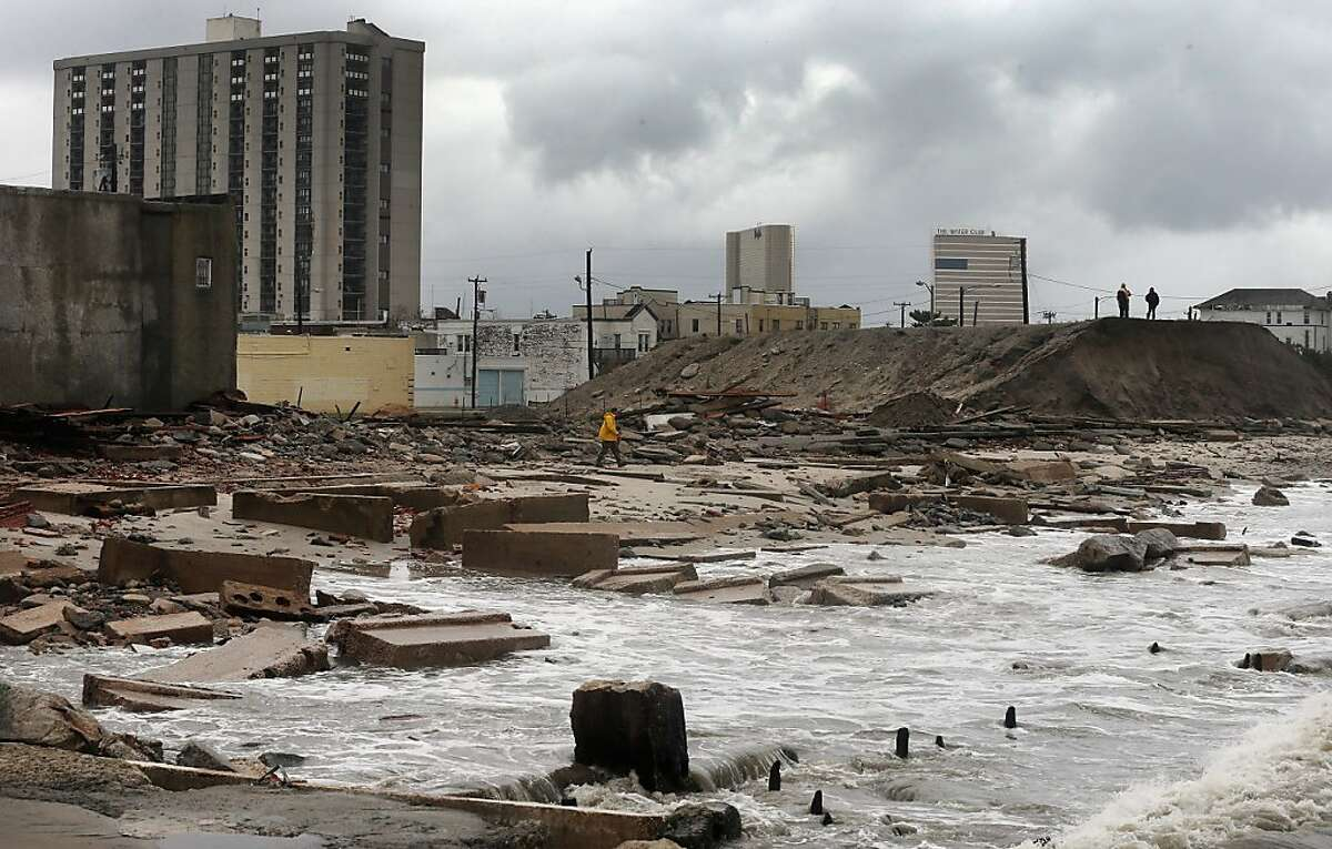 People stand on a mound of construction dirt to view the area where a 2,000-foot section of the