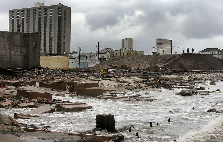 "People stand on a mound of construction dirt to view the area where a 2,000-foot section of the ""uptown"" boardwalk was destroyed by flooding from Hurricane Sandy on October 30, 2012 in Atlantic City, New Jersey. The storm has claimed at least 33 lives in the United States, and has caused massive flooding across much of the Atlantic seaboard. President Barack Obama has declared the situation a 'major disaster' for large areas of the US East Coast including New York City. Photo: Mario Tama, Getty Images"