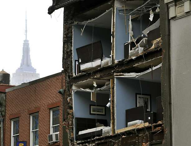 The Empire State Building towers in the background of an apartment buliding in Chelsea, New York City, with the facade broken off October 30, 2012  the morning after Hurricane Sandy.  The death toll from superstorm Sandy has risen to 16 in the mainland United States and Canada, and was expected to climb further as several people were still missing, officials said Tuesday.  Connecticut, New York, New Jersey, Maryland, Pennsylvania, West Virginia and North Carolina reported 15 dead from the massive storm system, and Toronto police said a Canadian woman was killed by flying debris. Photo: Timothy A. Clary, AFP/Getty Images