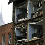 The Empire State Building towers in the background of an apartment buliding in Chelsea, New York City, with the facade broken off October 30, 2012  the morning after Hurricane Sandy.  The death toll from superstorm Sandy has risen to 16 in the mainland United States and Canada, and was expected to climb further as several people were still missing, officials said Tuesday.  Connecticut, New York, New Jersey, Maryland, Pennsylvania, West Virginia and North Carolina reported 15 dead from the massive storm system, and Toronto police said a Canadian woman was killed by flying debris.