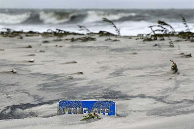 A keep off the dunes sign is buried Tuesday morning, Oct. 29, 2012, in Cape May, N.J., after a storm surge from superstormSandy pushed the Atlantic Ocean over the beach and into the streets. The storm that made landfall in New Jersey on Monday evening with 80 mph sustained winds killed at least 16 people in seven states, cut power to more than 7.4 million homes and businesses from the Carolinas to Ohio, caused scares at two nuclear power plants and stopped the presidential campaign cold. Photo: Mel Evans, Associated Press