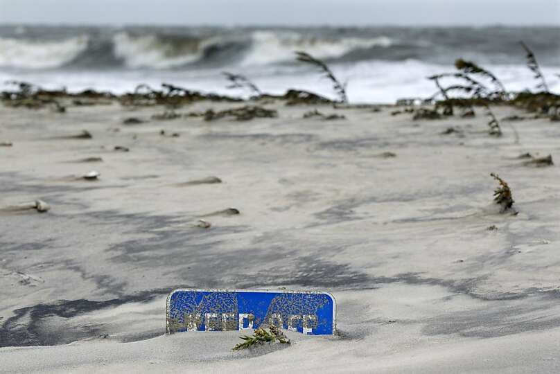 A keep off the dunes sign is buried Tuesday morning, Oct. 29, 2012, in Cape May, N.J., after a storm