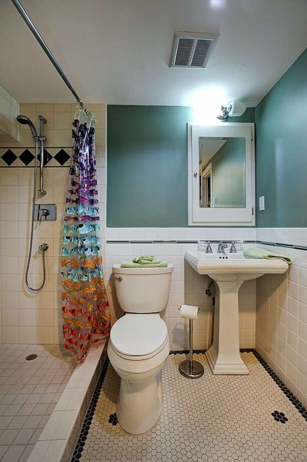 Three-quarter bathroom of 3015 28th Ave. W. The 3,090-square-foot brick Tudor, built in 1930, has four bedrooms, 2.25 bathrooms, coved ceilings, mahogany trim, French doors, a lower-level rec room with a fireplace, a deck, and water and mountain views on a 6,000-square-foot lot. It's listed for $849,900. Photo: Gordon Wang/Courtesy Marta Brace/Admiral Realty