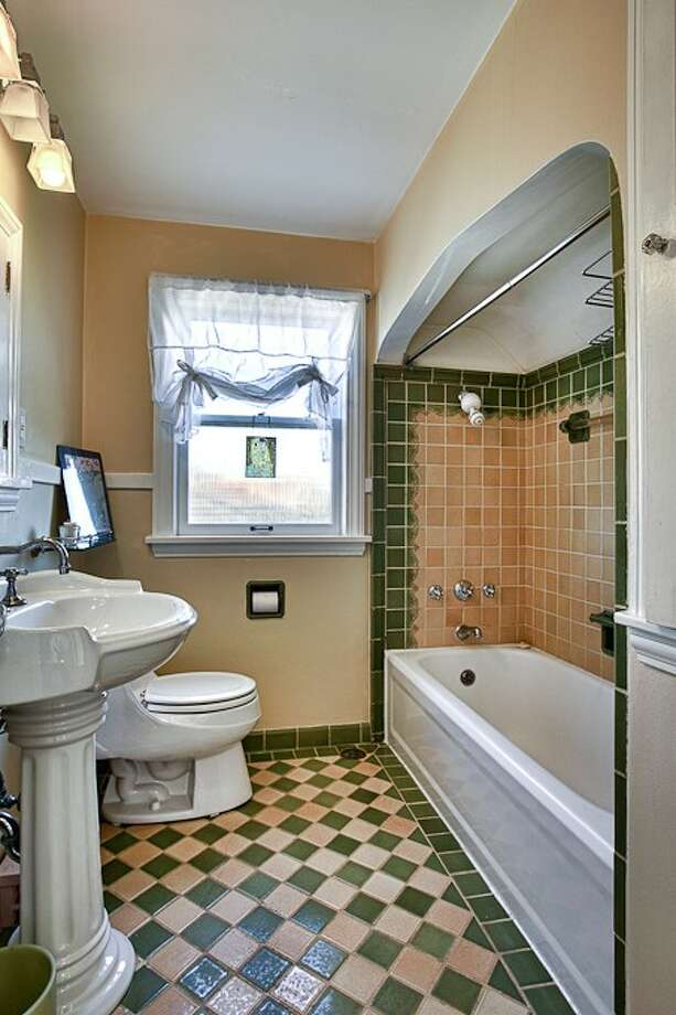 Bathroom of 3015 28th Ave. W. The 3,090-square-foot brick Tudor, built in 1930, has four bedrooms, 2.25 bathrooms, coved ceilings, mahogany trim, French doors, a lower-level rec room with a fireplace, a deck, and water and mountain views on a 6,000-square-foot lot. It's listed for $849,900. Photo: Gordon Wang/Courtesy Marta Brace/Admiral Realty