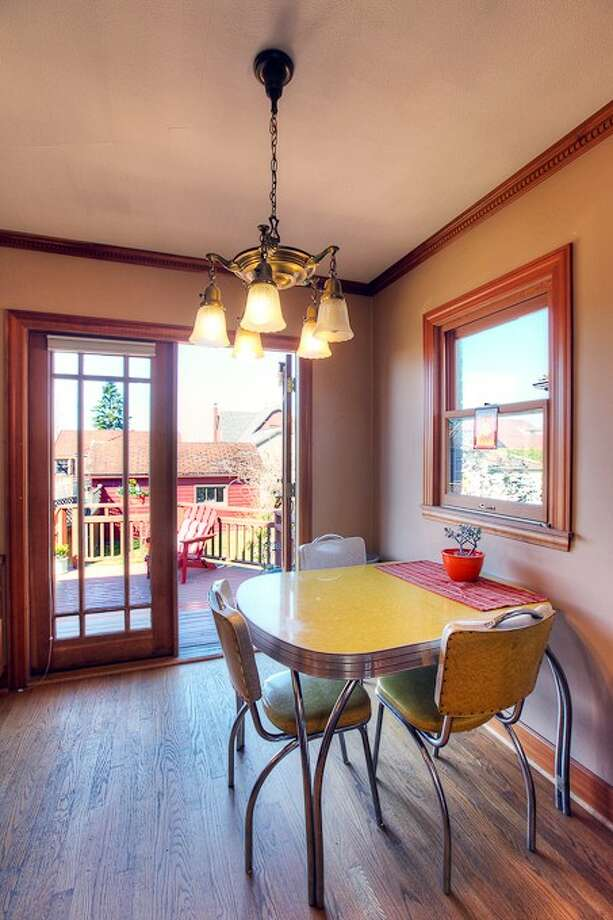 Eating area of 3015 28th Ave. W. The 3,090-square-foot brick Tudor, built in 1930, has four bedrooms, 2.25 bathrooms, coved ceilings, mahogany trim, French doors, a lower-level rec room with a fireplace, a deck, and water and mountain views on a 6,000-square-foot lot. It's listed for $849,900. Photo: Gordon Wang/Courtesy Marta Brace/Admiral Realty