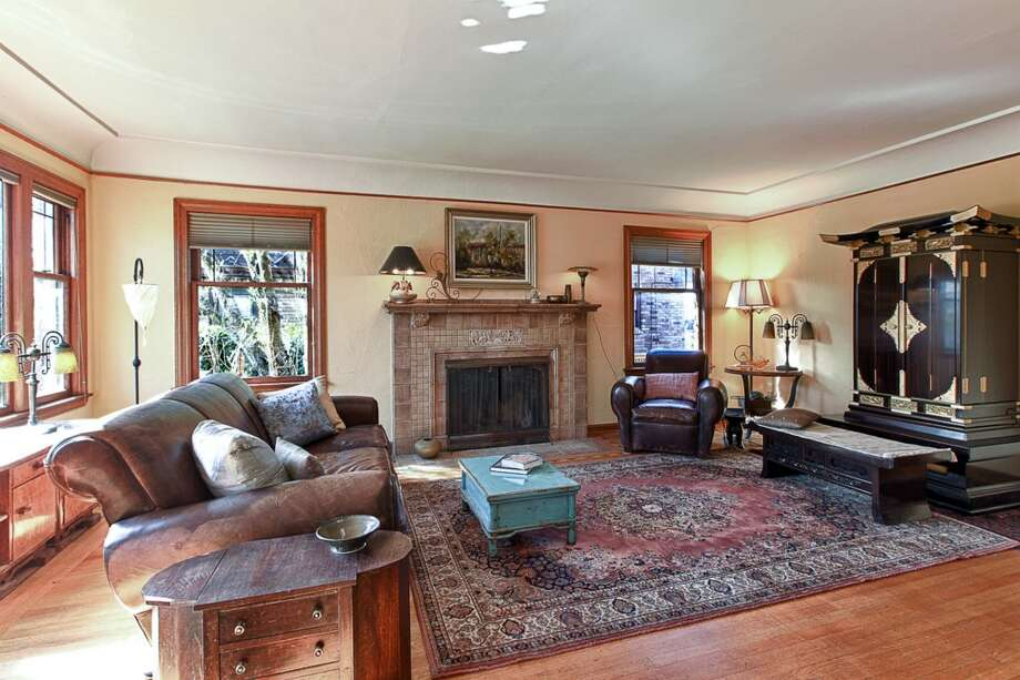 Living room of 3015 28th Ave. W. The 3,090-square-foot brick Tudor, built in 1930, has four bedrooms, 2.25 bathrooms, coved ceilings, mahogany trim, French doors, a lower-level rec room with a fireplace, a deck, and water and mountain views on a 6,000-square-foot lot. It's listed for $849,900. Photo: Gordon Wang/Courtesy Marta Brace/Admiral Realty