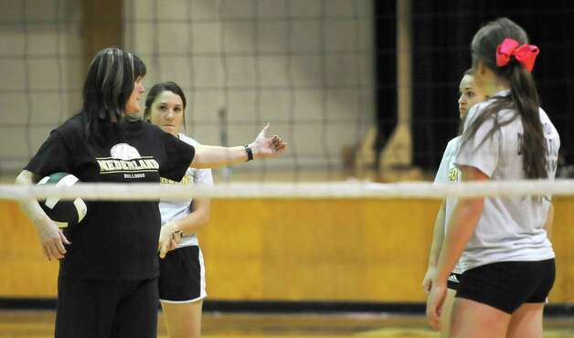 Head Coach Toni Leach, left,  gives specific directions to some of the girls as they form sides to scrimmage each other.  The Nederland girls volleyball team is in the playoffs again this season and will be playing Barbers Hill on Tuesday. They were practicing for the game Monday afternoon in the gym under the direction of 32 year veteran coach Toni Leach. Dave Ryan/The Enterprise