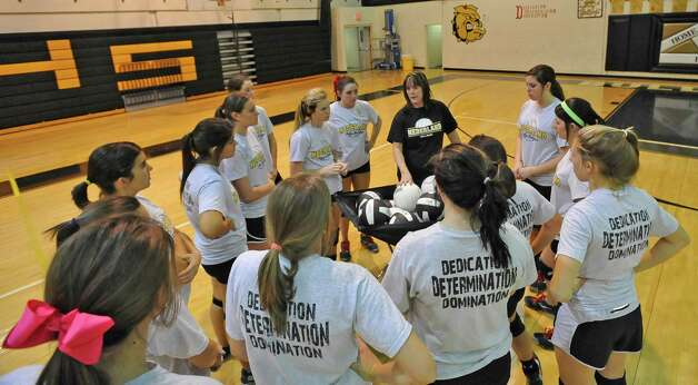 Head Coach Toni Leach,center, in black shirt, talks to the team about the team they will face on Tuesday. The Nederland girls volleyball team is in the playoffs again this season and will be playing Barbers Hill on Tuesday. They were practicing for the game Monday afternoon in the gym under the direction of 32 year veteran coach Toni Leach. Dave Ryan/The Enterprise Photo: Dave Ryan