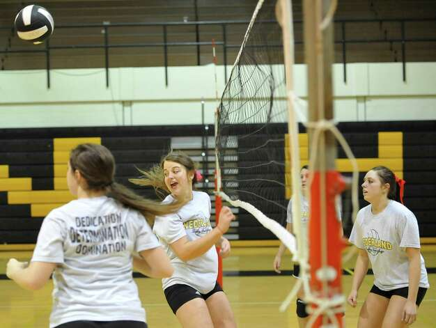 Kelsey Beard, center right, watches the ball sail towards one of her teammates. The Nederland girls volleyball team is in the playoffs again this season and will be playing Barbers Hill on Tuesday. They were practicing for the game Monday afternoon in the gym under the direction of 32 year veteran coach Toni Leach. Dave Ryan/The Enterprise Photo: Dave Ryan