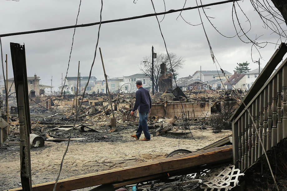 NEW YORK, NY - OCTOBER 30:  A fire inspector walks through a neighborhood destroyed during Hurricane Sandy October 30, 2012 in the Breezy Point neighborhood of the Queens borough of New York City. At least a few dozen people were reported killed in the United States by Sandy as millions of people in the eastern United States have awoken to widespread power outages, flooded homes and downed trees. New York City was hit especially hard with widespread power outages and significant flooding in parts of the city. Photo: Spencer Platt, Getty Images / 2012 Getty Images