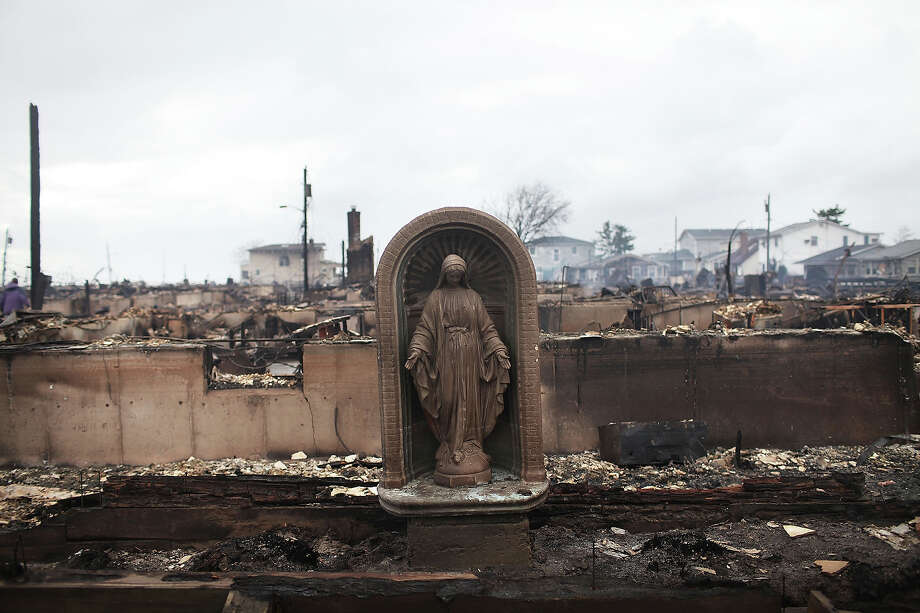 NEW YORK, NY - OCTOBER 30: A Virgin Mary is all that remains from a home which was destroyed during Hurricane Sandy in Breezy Point, Queens on October 30, 2012 in New York, United States. Over 50 homes wer destroyed in a late night and fast moving fire. At least 15 people were reported killed in the United States by Sandy as millions of people in the eastern United States have awoken to widespread power outages, flooded homes and downed trees. New York City was hit especially hard with wide spread power outages and significant flooding in parts of the city. Photo: Spencer Platt, Getty Images / 2012 Getty Images