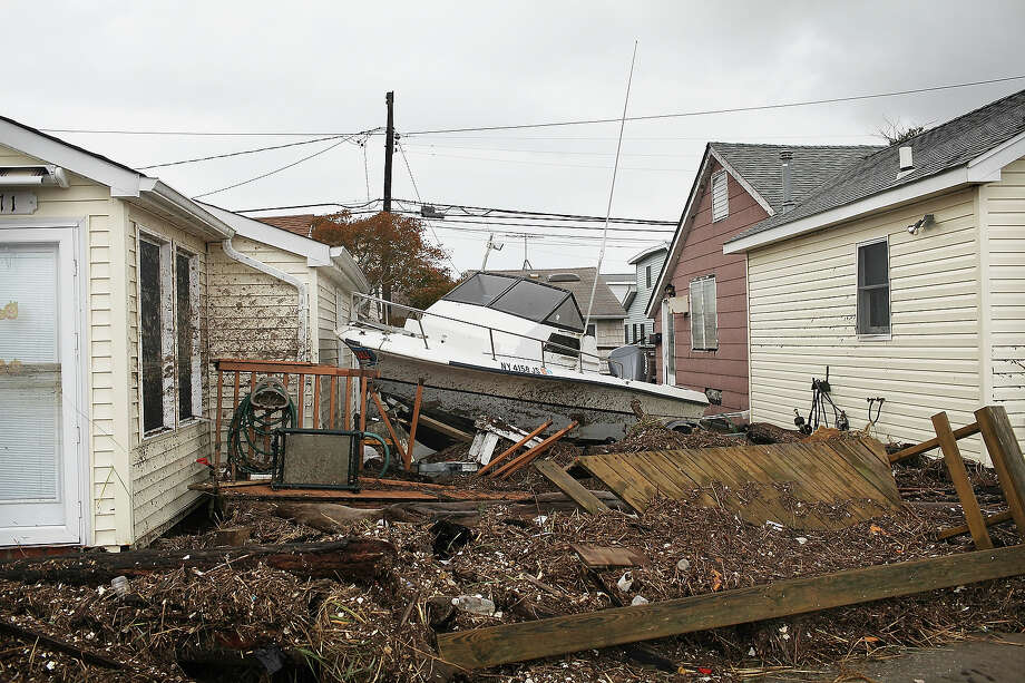 NEW YORK, NY - OCTOBER 30: A boat washed up in the storm surge sits between houses on October 30, 2012 in the Breezy Point neighborhood of the Queens borough of New York City. At least two dozen people were reported killed in the United States by Sandy as millions of people in the eastern United States have awoken to widespread power outages, flooded homes and downed trees. New York City was hit especially hard with widespread power outages and significant flooding in parts of the city. Photo: Spencer Platt, Getty Images / 2012 Getty Images