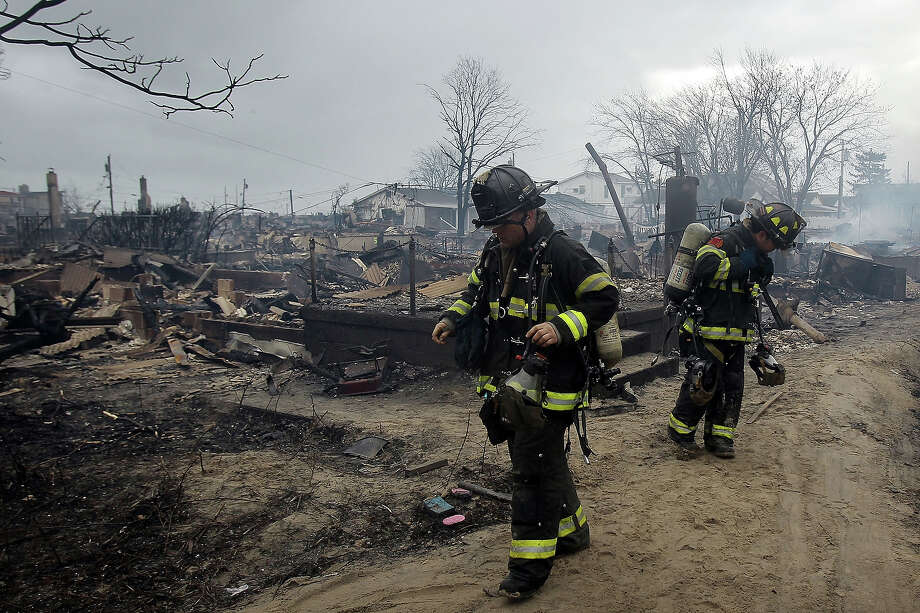 NEW YORK, NY - OCTOBER 30:  Firefighters work to contain a fire that destroyed over 50 homes during Hurricane Sandy on October 30, 2012 in the Breezy Point neighborhood of the Queens borough of New York.  At least 33 people were reported killed in the United States by Sandy as millions of people in the eastern United States have awoken to widespread power outages, flooded homes and downed trees. New York City was hit especially hard with wide spread power outages and significant flooding in parts of the city. Photo: Spencer Platt, Getty Images / 2012 Getty Images