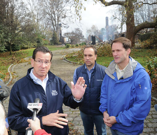 Gov. Dannel P. Malloy, left, speaks with the media at the scene of the aftermath of a house fire at 44 Binney Lane in Old Greenwich the day after Hurricane Sandy hit Old Greenwich, Tuesday afternoon, Oct. 30, 2012. At  center is Greenwich First Selectman Peter Tesei, at right is Congressman Jim  Himes. Photo: Bob Luckey / Greenwich Time