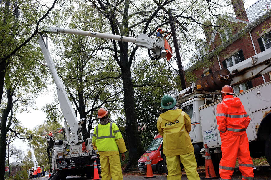 Workers from local power company Pepco repair power lines in the Woodley Park neighborhood in the wake of Hurricane Sandy on October 30, 2012 in Washington. The death toll from superstorm Sandy has risen to 32 in the United States and Canada, and was expected to climb further as several people remained missing, officials said. Officials in the states of Connecticut, Maryland, New York, New Jersey, North Carolina, Pennsylvania, Virginia and West Virginia all reported deaths from the massive storm system, while Toronto police said a Canadian woman was killed by flying debris.  AFP PHOTO/Mandel NGAN Photo: MANDEL NGAN, AFP/Getty Images / 2012 AFP