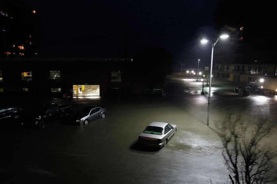 "LONG BEACH, NY - OCTOBER 30:  Flood water runs down West Broadway engulfing parked cars during Hurricane Sandy on October 30, 2012 in Long Beach, New York. The storm has claimed at least 33 lives in the United States, and has caused massive flooding across much of the Atlantic seaboard. U.S. President Barack Obama has declared the situation a ""major disaster"" for large areas of the U.S. east coast, including New York City, with widespread power outages and significant flooding in parts of the city. Photo: Mike Stobe, Getty Images / 2012 Getty Images"