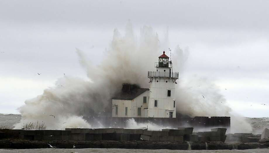 Waves pound a lighthouse on the shores of Lake Erie Tuesday, Oct. 30, 2012, near Cleveland. High winds spinning off the edge of superstorm Sandy took a vicious swipe at northeast Ohio early Tuesday, uprooting trees, cutting power to hundreds of thousands, closing schools and flooding parts of major commuter arteries that run along Lake Erie. (AP Photo/Tony Dejak) Photo: Tony Dejak, Associated Press