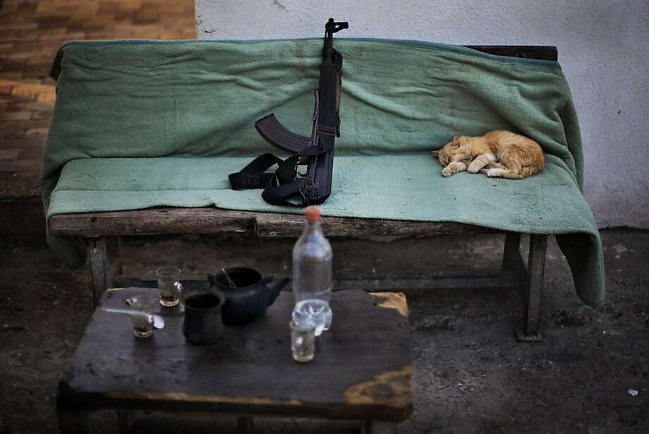 Guns and whiskers:An unreliable guard falls asleep on the job at a Hamas security checkpoint in Gaza City. Photo: Bernat Armangue, Associated Press