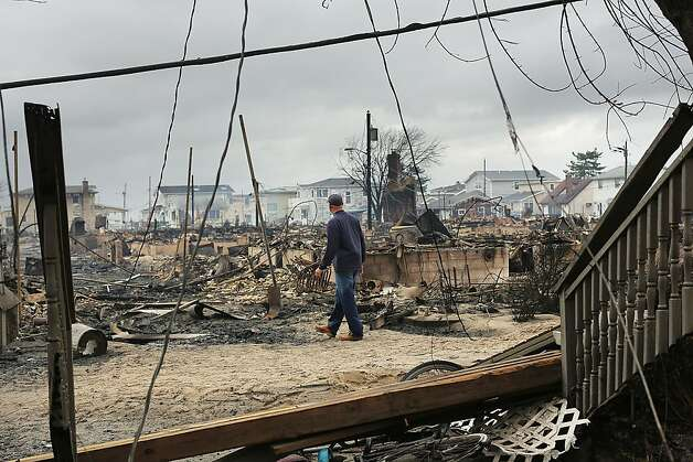 A fire inspector walks through a neighborhood destroyed during Hurricane Sandy October 30, 2012 in the Breezy Point neighborhood of the Queens borough of New York City. At least a few dozen people were reported killed in the United States by Sandy as millions of people in the eastern United States have awoken to widespread power outages, flooded homes and downed trees. New York City was hit especially hard with widespread power outages and significant flooding in parts of the city. Photo: Spencer Platt, Getty Images