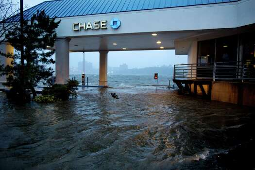 Rising water from the Hudson River overtakes a bank drive-through in Edgewater, N.J., Monday, Oct. 29, 2012 as Hurricane Sandy lashed the East Coast. The powerful storm made the westward lurch and took dead aim at New Jersey and Delaware on Monday, washing away part of the Atlantic City boardwalk, putting the presidential campaign on hold and threatening to cripple Wall Street and the New York subway system with an epic surge of seawater. (AP Photo/Craig Ruttle) Photo: Craig Ruttle, Associated Press / FR61802 AP