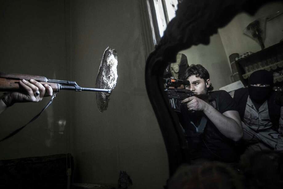 A rebel sniper aims as another rebel fighter is reflected in a mirror in Aleppo, Syria. Airstrikes and shells from tanks killed at least 23 people Tuesday. Photo: Narciso Contreras, Associated Press / AP