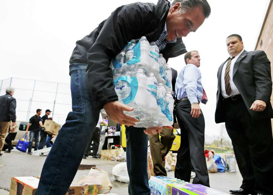 Republican presidential candidate, former Massachusetts Gov. Mitt Romney lifts bottles of water to load into a truck as he participates in a campaign event collecting supplies from residents and local relief organizations for victims of superstorm Sandy,Tuesday, Oct. 30, 2012, at the James S. Trent Arena in Kettering, Ohio. (AP Photo/Charles Dharapak) Photo: Charles Dharapak, STF / AP