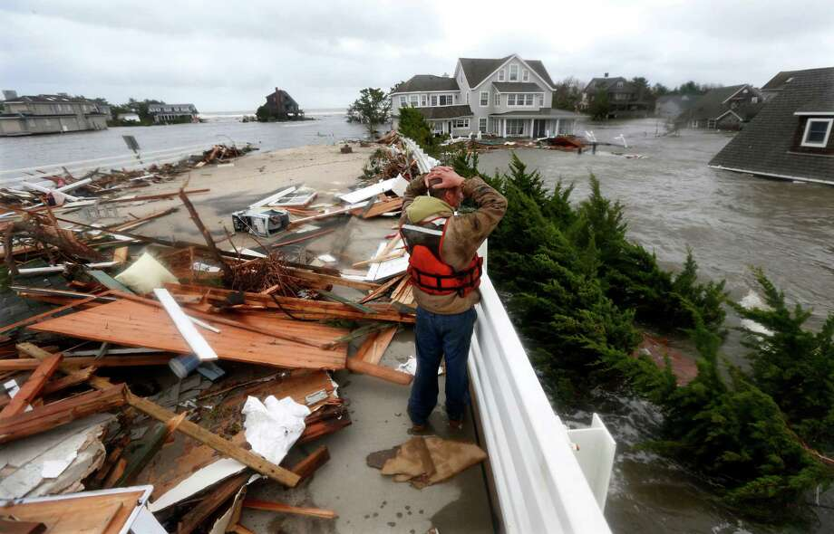 Brian Hajeski, 41, of Brick, N.J., reacts as he looks at debris of a home that washed up on to the Mantoloking Bridge the morning after superstorm Sandy rolled through, Tuesday, Oct. 30, 2012, in Mantoloking, N.J. Sandy, the storm that made landfall Monday, caused multiple fatalities, halted mass transit and cut power to more than 6 million homes and businesses. (AP Photo/Julio Cortez) Photo: Julio Cortez, Associated Press / AP