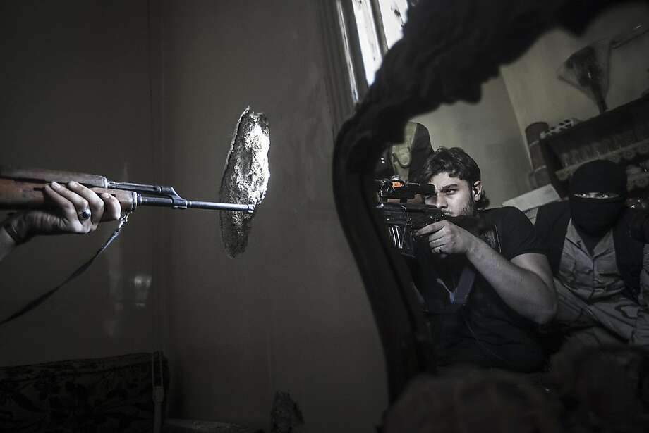 Hole-in-the-wall sniper:A rebel sharpshooter takes aim at a Syrian army position in a residential building in the Jedida district of Aleppo. Photo: Narciso Contreras, Associated Press