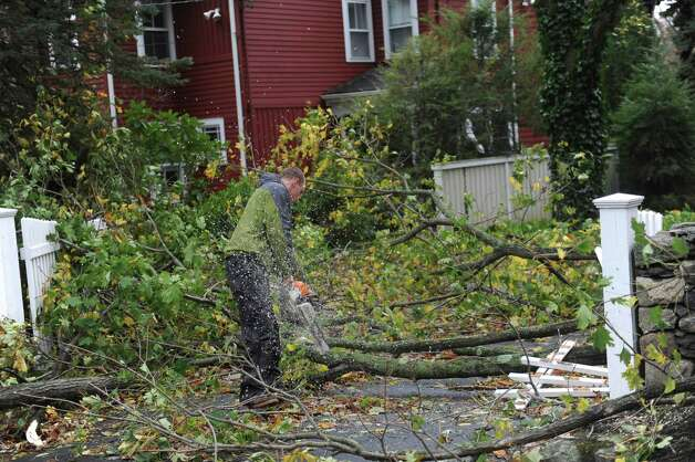 Todd Ferber, of Stamford, cuts wood for a client after the storm from Hurricane Sandy in Old Greenwich, Conn. on Tuesday, Oct. 30, 2012. Photo: Helen Neafsey / Old Greenwich