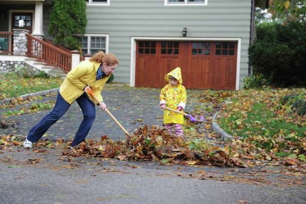 Kristen Bodenstein works with her daughter Sarah, 4,to clean up on Tuesday Oct. 31, 2012, after weather from Hurricane Sandy. The storm dumped debris in their yard on Irvine Road, in Old Greenwich, Conn. Photo: Helen Neafsey / Old Greenwich