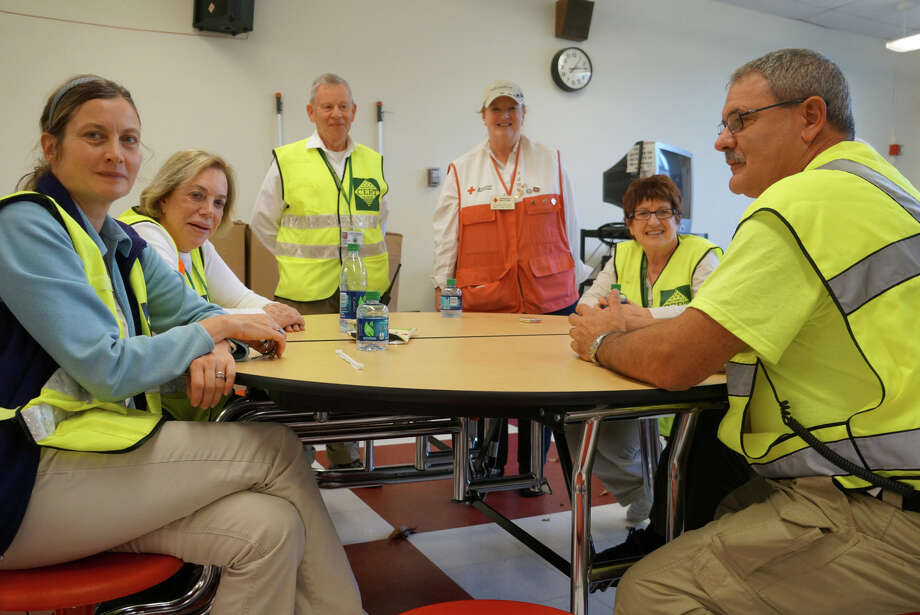 Mary Ann West, standing right, and Ernest Heidelberg, standing left, join other Community Emergency Response Team volunteers for a meeting Monday in the cafeteria of Long Lots Elementary School, which is housing the town's emergency shelter. Photo: Paul Schott