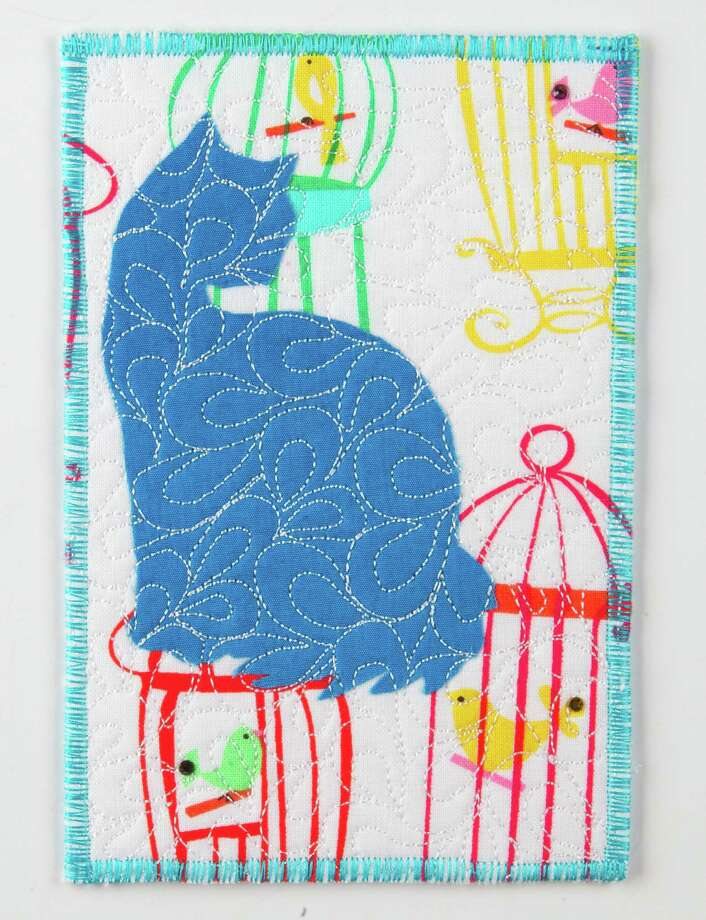 "A postcard made from fabric donated for the ""Pet Project,"" part of the International Quilt Festival is seen in the chronicle studio Monday, Oct. 29, 2012, in Houston. Quilters have donated more than 600 handmade fabric postcards for a fundraiser for Friends for Life, Houston's no-kill animal shelter. The postcards will be sold for $20 each; the money will go to Friends for Life. (Cody Duty / Houston Chronicle) Photo: Cody Duty, Staff / Houston Chronicle"