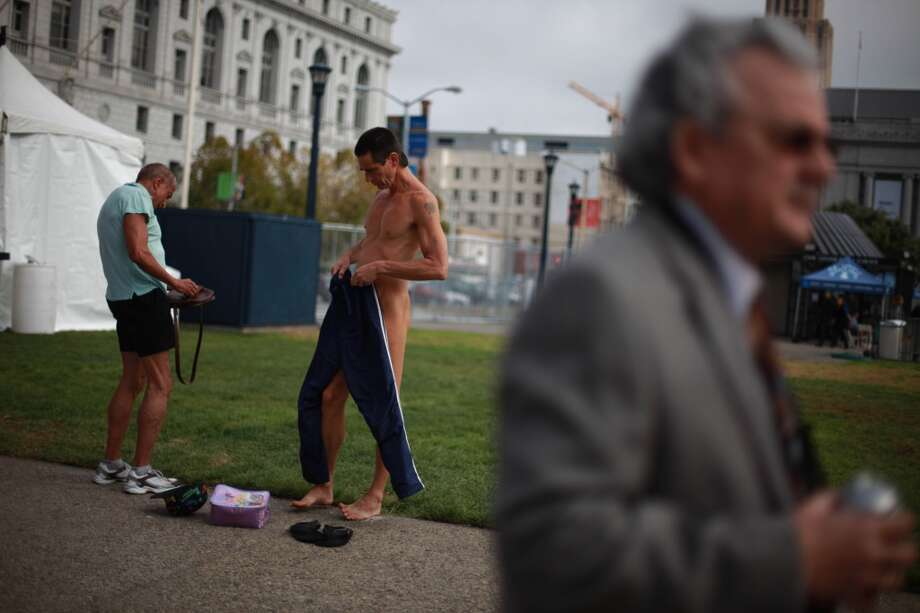 Rusty Mills (let) and Lloyd Fishback (center), both of San Francisco, remove their clothes across from City Hall as they and other demonstrators gather to  protest Supervisor Scott Weiner's proposal to restrict public  nudity in the city  on Tuesday, October 30, 2012 in San Francisco, Calif.