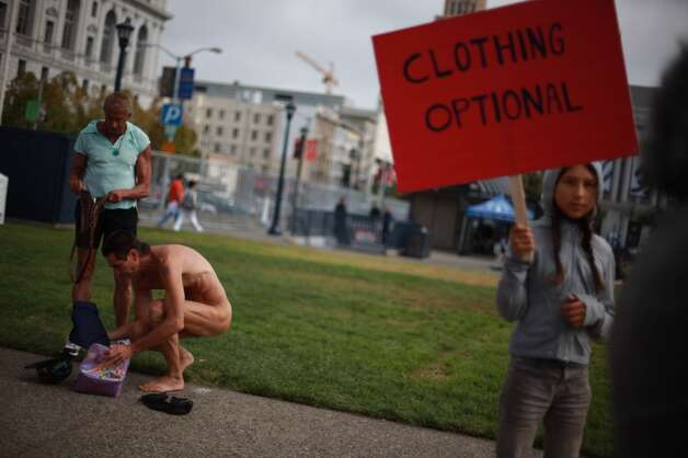 Rusty Mills (let) and Lloyd Fishback (center), both of San Francisco, remove their clothes across from City Hall as they and other demonstrators gather to  protest Supervisor Scott Weiner's proposal to restrict public  nudity in the city  on Tuesday, October 30, 2012 in San Francisco, Calif. (The Chronicle) / SF