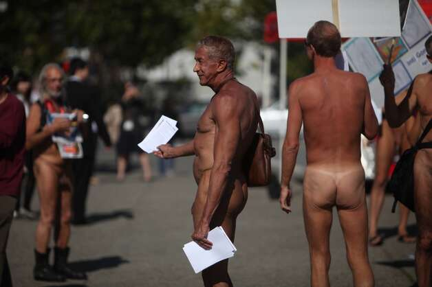 Rusty Mills (center) of San Francisco, hands out leaflets across from City Hall as he and other demonstrators gather to  protest Supervisor Scott Weiner's proposal to ban nudity in the city except at certain functions on Tuesday, October 30, 2012 in San Francisco, Calif.