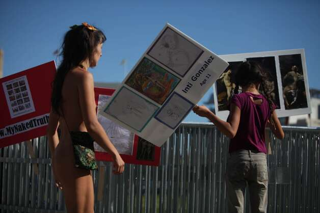 Gypsy Taub (l to r) organizes signs as her daughter Inti Gonzalez, 11, carries one she and her brother made as they gather with other demonstrators gather to  protest Supervisor Scott Weiner's proposal to restrict public  nudity in the city on Tuesday, October 30, 2012 in San Francisco, Calif.